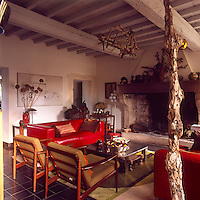 A country sitting room with a painted beamed ceiling and a large inglenook fireplace. The room is furnished with modern red leather sofas, a metal coffee table and 1950's style all of which stand on a green patterned rug.