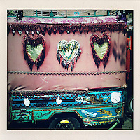 A lorry's canopy decorated with flowers and giant hearts.