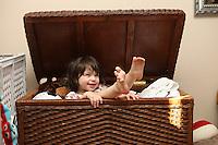 Child enjoys playing in wicker basket.