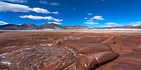 Amazing volcanic stones of the Salar de Aguas Calliente with the 5592m-high, snow-capped Láscar Volcano under a blue sky, San Pedro de Atacama, Chile