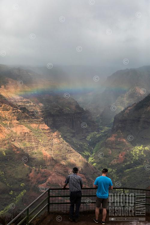 Two men enjoy the overview of Wamea Canyon with a rainbow, Kaua'i.