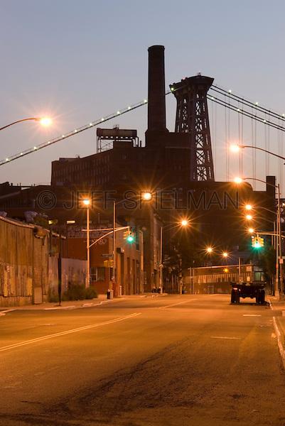 Street Scene at Dusk in the Williamsburg Neighborhood of Brooklyn, Williamsburg Bridge and former Domino Sugar Factory in the background..New York City, New York State, USA
