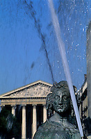 Water fountain and sculpture with La Madeleine church in the background, Paris, France.