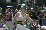 WOMEN ON BIKE IN JESTER HAT AND BEADS AT GAY PRIDE PARADE