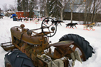 Tollef Monson runs down the road past a dilapidated tractor as he arrives in Shageluk on Friday afternoon