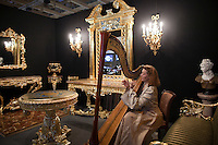 Moscow, Russia, 25/10/2009..A woman plays the harp in a luxury furnishings display at the Millionaire Fair in Moscow. The event has become an annual fixture, attracting thousands of would-be and existing Russian millionaires to view and purchase a wide range of luxury goods. This year however the fair was much smaller, an indication of how the formerly booming Russian economy has been hit by the world financial crisis.
