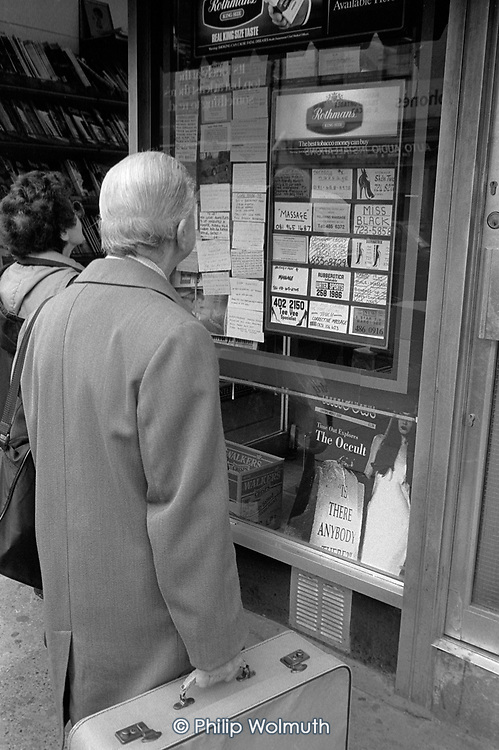 Man with a suitcase looks at notices in a newsagent's window advertising rooms for rent and sex worker services, Kings Cross, London 1990.