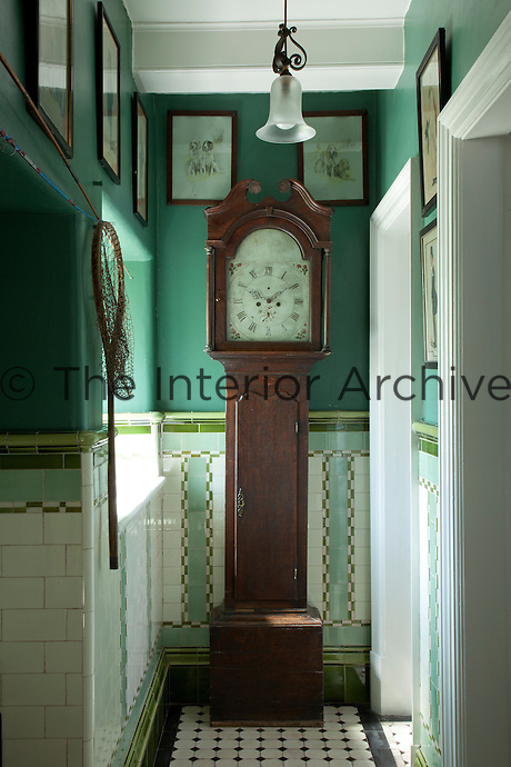 An antique grandfather clock tucked away in one of the bathrooms, surrounded by illustrations of dogs