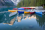 """Mountains surrounding Moraine Lake reflect into calm waters as canoes rest on the dock and in the lake, Banff National Park, Alberta, Canada<br /> <br /> Third Place, """"Outdoor Fun and Adventure Category"""" in the 2013 Outdoor Writers Association of America """"Excellence in Craft"""" awards"""