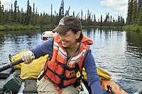 Georgia Bennett rows downriver along a slow stretch of Alaska's Gulkana River.