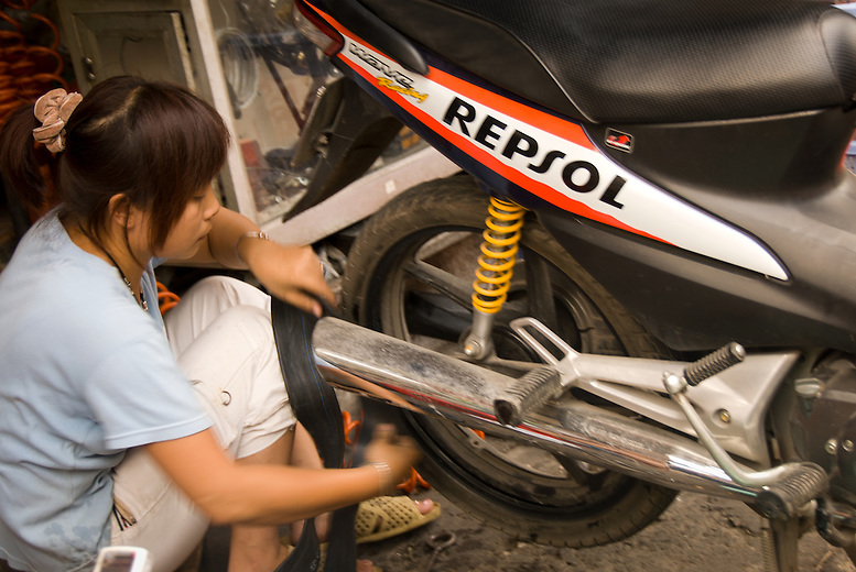 A young woman fixes a motorbike tire in Hanoi, Vietnam.  Young women take on many traditionally male dominated tasks and jobs in vietnam such as fixing motorbikes and repairing roads.