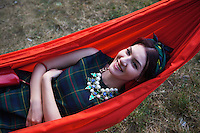 """Romania. Iași County. Iasi. A stylish and smiling woman is lying in a red hamac during the festival """" Street Delivery. Global Warning"""" which takes place in the Pogor garden near the museum """"Vasile Pogor"""", a literary history museum which is part of the Iași Romanian Literature Museum ( Muzeul Literaturii Romane Iasi). Iași (also referred to as Iasi, Jassy or Iassy) is the largest city in eastern Romania and the seat of Iași County. Located in the Moldavia region, Iași has traditionally been one of the leading centres of Romanian social life. The city was the capital of the Principality of Moldavia from 1564 to 1859, then of the United Principalities from 1859 to 1862, and the capital of Romania from 1916 to 1918. 13.06.15 © 2015 Didier Ruef"""