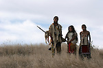 Three young Native American Indian boys standing in the tall grass of South Dakota.  One boy retying his leather pouch
