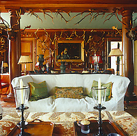 A sofa dressed in a white loose cover strikes a note of informality in the panelled sitting room