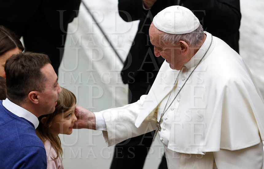 Pope Francis caresses a child at the end of his weekly general audience in the Paul VI hall at the Vatican, January 22, 2020.<br />