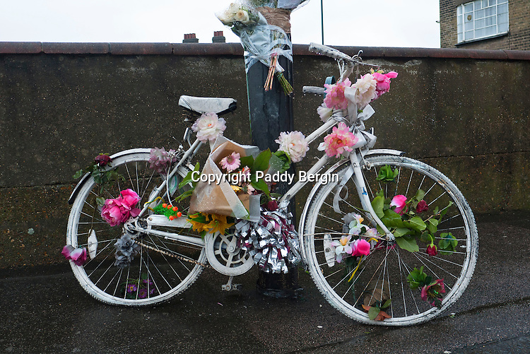 """A ghost bike (also referred to as a ghostcycle or WhiteCycle) is a bicycle roadside memorial, placed where a cyclist has been killed or severely injured, usually by a motor vehicle.<br /> <br /> Apart from being a memorial, it is usually intended as a reminder to passing motorists to share the road. Ghost bikes are usually junk bicycles painted white, sometimes with a placard attached, and locked to a suitable object close to the scene of the accident. They are also sometimes stripped of their tires, to deter theft.<br /> <br /> According to The Guardian, the first recorded ghost bike was in St. Louis, Missouri, in 2003. A witness to a collision between a cyclist and a car placed a painted bike at the location with a message that read: """"Cyclist struck here"""".<br /> <br /> The original idea of painting bikes white reportedly goes back to the city of Amsterdam in the 1960s as an anarchist project to liberate two-wheel transport—white bikes were free, help yourself and then leave it for someone else.<br /> <br /> The ghost bike idea in the United States may have originated with a project by San Francisco artist Jo Slota, begun in April 2002. This was a purely artistic endeavour. Slota was intrigued by the abandoned bicycles that he found around the city, locked up but stripped of useful parts. He began painting them white, and posted photographs on his website, ghostbike.net. As the idea was taken up for different purposes, Slota faced a dilemma. San Francisco is one of the safer U.S. cities for bicyclists, but memorial ghost bikes sprang up there as elsewhere, changing perceptions of his project.<br /> <br /> Stock Photo by Paddy Bergin"""