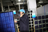 CHINA. Hebei.  Ma Xuelu, the president of the Low Carbon City Research Association of Baoding City inside one of the city's solar panel factories. The city is the world's first 'carbon positive' town. The town's main industires focus on producing wind and solar technologies. 2009