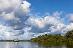 Navigation sur le Rio Negro au nord de Manaus sur le bateau de croisière La JangadaL Les nuages et le bateau se reflètent dans les eaux noires du Rio Negro