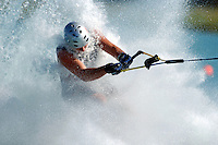 Barefoot waterskier is splashed by all the water spray coming up off the wake.