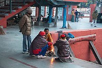 India, Dehradun.  Men Warming themselves by a Fire at the Dehradun Train Station on a Cold Winter Morning.