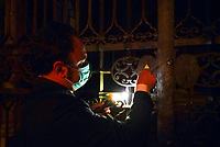 """Gianni Crea, the Vatican Museums chief """"Clavigero"""" key-keeper, opens a gate that leads to one of the museum's sections, at the Vatican, Monday, Feb. 1, 2021. Crea is the """"clavigero"""" of the Vatican Museums, the chief key-keeper whose job begins each morning at 5 a.m., opening the doors and turning on the lights through 7 kilometers of one of the world's greatest collections of art and antiquities. The Associated Press followed Crea on his rounds the first day the museum reopened to the public, joining him in the underground """"bunker"""" where the 2,797 keys to the Vatican treasures are kept in wall safes overnight. (AP Photo/Andrew Medichini)"""