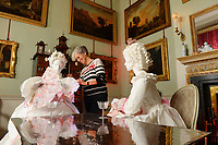 """BNPS.co.uk (01202 558833)<br /> Pic: ZacharyCulpin/BNPS<br /> <br /> Denise applies the finishing touches to one of the stunning paper dresses. <br /> <br /> Ori-garments -  Artist Denise Watson has created a stunning 1750's masquerade Christmas Ball with characters made entirely from paper at the National Trust's Uppark House in West Sussex.<br /> <br /> Denise has dressed 14 shop mannequins with clothes, shoes, masks, fans, floral details, hair and even jewellery made from things like tissue paper, gift wrap and brown parcel paper. <br /> <br /> The festive display was inspired by Admiral Lord Gambier's memoirs in which he quotes from Lady Sarah Featherstonhaugh's journal of 1753 where she wrote: """" The whole party afterwards proceed to Uppark, where they passed a cheerful happy Christmas in the most friendly society, and enlivened their neighbourhood with some masked balls.""""<br />  <br /> The design to the finished result took a total of three months. Denise said, """"I am really delighted with the final result. It has been a joy to work at Uppark using the grand rooms and to recreate an event which actually took place""""."""