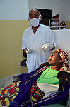 A patient winces moments after her dentist extracts a tooth at Kinigi District Hospital, in northwest Rwanda.