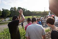 """Nach den pogromartigen Ausschreitungen gegen eine Fluechtlinsunterkunft im saechschen Heidenau am Freitag den 21. August 2015 durch Anwohnerinnen der Ortschaft, kamen am Samstag de 22. August 2015 ca. 250 Menschen in die Ortschaft um ihre Solidaritaet mit den Gefluechteten zu zeigen.<br /> Am Vorabend hatten Rassisten, Nazis und Hooligans sich zum Teil Strassenschlachten mit der Polizei geliefert um zu verhindern, dass Fluechtlinge in einen umgebauten Baumarkt einziehen. Ueber 30 Polizisten wurden dabei verletzt.<br /> Bis in die Abendstunden des 22. August blieb es trotz spuerbarer Anspannung um die Unterkunft ruhig. Im Laufe des Tages wurden immer wieder Gefluechtete mit Reisebussen gebracht was von den wartenenden Heidenauern mit Buh-Rufen begleitet wurde. Vereinzelt wurde auch """"Sieg Heil"""" gerufen, was die Polizei jedoch nicht verfolgte.<br /> Kurz vor 23 Uhr griffen Nazis und Hooligans dann wie am Vorabend die Polizei mit Steinen, Flaschen, Feuerwerkskoerpern und Baustellenmaterial an. Die Polizei mussten mehrfach den Rueckzug antreten, scheuchte den Mob dann von der Fluechtlingsunterkunft weg. Dabei wurden auch wieder Traenengasgranaten verschossen. Mindestens ein Nazi wurde festgenommen.<br /> Im Bild: Einige Gefluechtete trauen sich aus der Unterkunft und besuchen die antirassistische Kundgebung.<br /> 22.8.2015, Heidenau<br /> Copyright: Christian-Ditsch.de<br /> [Inhaltsveraendernde Manipulation des Fotos nur nach ausdruecklicher Genehmigung des Fotografen. Vereinbarungen ueber Abtretung von Persoenlichkeitsrechten/Model Release der abgebildeten Person/Personen liegen nicht vor. NO MODEL RELEASE! Nur fuer Redaktionelle Zwecke. Don't publish without copyright Christian-Ditsch.de, Veroeffentlichung nur mit Fotografennennung, sowie gegen Honorar, MwSt. und Beleg. Konto: I N G - D i B a, IBAN DE58500105175400192269, BIC INGDDEFFXXX, Kontakt: post@christian-ditsch.de<br /> Bei der Bearbeitung der Dateiinformationen darf die Urheberkennzeichnung in den EXIF- und """