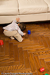 16 month old toddler boy looking under couch for lost toy Piaget object permanence vertical