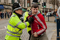 Saturday 05 April 2014<br /> Pictured: A White pride supporter is held back by police<br /> Re: White Pride and Anti Fascist groups protest in Swansea City Cebtre