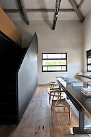 A functional, industrial space with exposed roof beams and a wood floor. The room is furnished with a long black iron table and light wood chairs. A staircase with a side panel leads to an upper floor.
