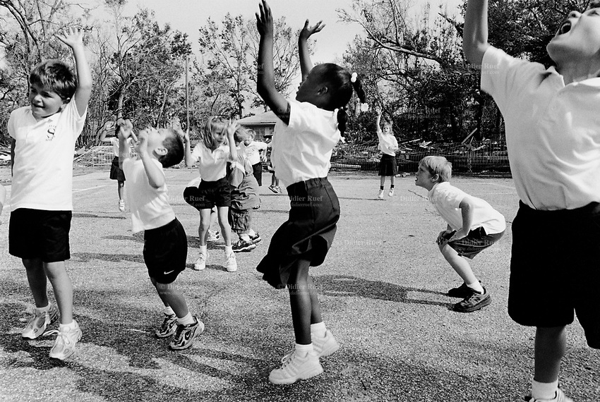USA. Mississippi. Biloxi. Aftermath of hurricane Katrina. Most houses were  destroyed by the storm, the tidal surge (water wave) and the floods. The Nativity Bum School did survive and has started again its classes. Gymnastics. Pupils jump in the air. © 2005 Didier Ruef