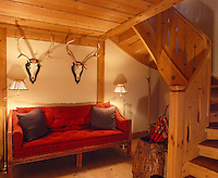 Sets of antlers are displayed on the wall above the red velvet sofa in the hall