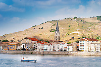 The town Tain l'Hermitage, the riverside side, the river Rhone. A sailing boat on the water.   The Hermitage vineyards on the hill behind the city Tain-l'Hermitage, on the steep sloping hill, stone terraced. Sometimes spelled Ermitage.  Tain l'Hermitage, Drome, Drôme, France, Europe