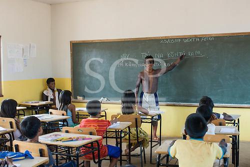 Ngoiwere Village, Mato Grosso State, Brazil. Kisedje (Suya), Tenpty Kisedje, teacher and school director, teaching children to write in their taditional language, Ge, in the village school.
