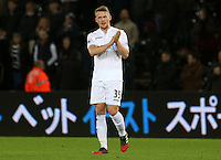 Stephen Kingsley of Swansea City FC applauds the Swansea fans as he leaves the field looking dejected following the final whistle of the Premier League match between Swansea City and West Ham United at The Liberty Stadium, Swansea, Wales, UK. 26 December 2016