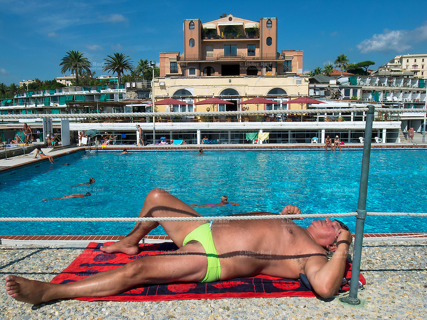 Italy. Liguria Province. Genova. Nuovo Lido beach resort. An old man is sunbathing while people are swimming in the pool. 18.08.13 © 2013 Didier Ruef