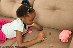 6 year old girl at home on couch counting sorting coins from piggy bank