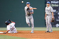 Shortstop Patrick Valaika (16) of the Asheville Tourists turns a double play, as Tzu-Wei Lin (36) of the Greenville Drive tries to break it up in a game on Monday, April 21, 2014, at Fluor Field at the West End in Greenville, South Carolina. Second baseman Michael Benjamin is at right. Greenville won, 8-3. (Tom Priddy/Four Seam Images)