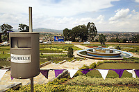 """Rwanda. Kigali province. Kigali. Downtown. Traffic circle in the town center. Water fountain.Public dustbin. Trash can means """"poubelle"""". The small triangle flags, white and mallow, are for the 13th commemoration of the Genocide. Mauve is the color of mourning. © 2007 Didier Ruef"""