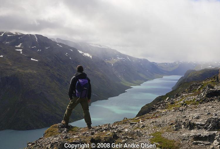 Man overlooking Lake Gjende during the famous walk Besseggen in Jotunheimen mountain range in Norway