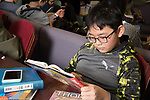 Male student reading book in library public school for the gifted