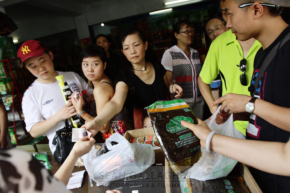 """Tourists in a gift shop whilst visiting the bamboo forests of Zhuhai, which literally translates as """"Bamboo Sea."""" This is one of the few areas of bamboo forest in the south that have a moderate amount of protection. Felling still occurs, as the forests do not fall within the 1998 logging ban."""