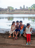 These local Khmer child vendors selling souvenirs to tourist at Angkor Wat, In awe and playing, watching something on the cellphone. Times have changed in Cambodia.