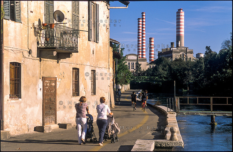 Turbigo (Milano), la centrale termoelettrica e due donne con passeggino davanti a una vecchia casa lungo il Naviglio Grande --- Turbigo (Milan), the thermoelectric power plant and two women with stroller in front of an old house along the Naviglio Grande canal
