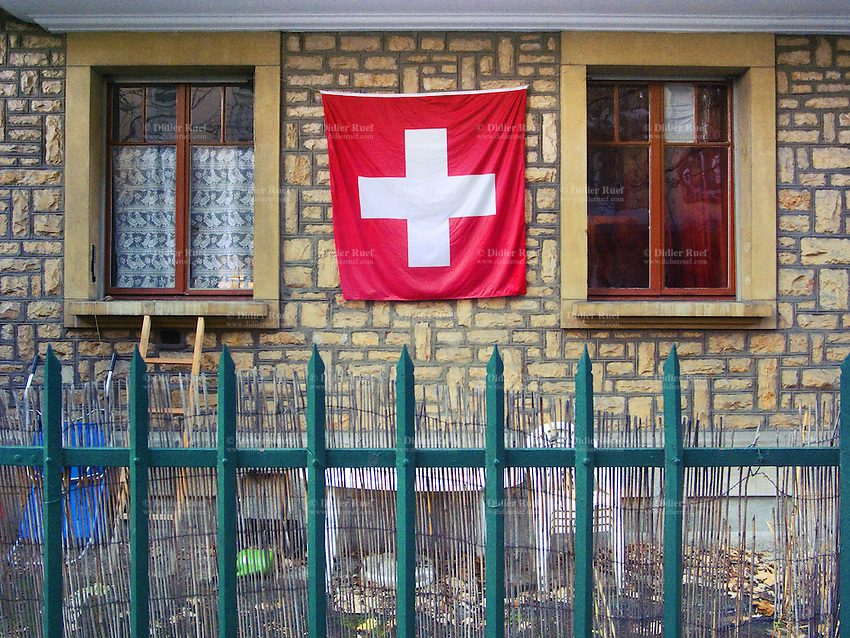 Switzerland. Geneva. Swiss flag and green metal fence. Private property. 26.11.09  © 2009 Didier Ruef