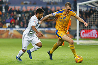 (L-R) Wayne Routledge of Swansea City challenges Dan Burn of Wigan Athletic during the Sky Bet Championship match between Swansea City and Wigan Athletic at the Liberty Stadium, Swansea, Wales, UK. Saturday 29 December 2018