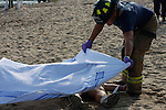 A firefighter placing a white sheet over a victim that had deceased