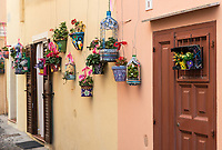 Hand painted planters and colorful flowers adorn a charming street,, Alghero,, Sardinia, Italy.