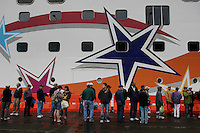 Tourists wait to board the cruise ship after a rainy afternoon in Ketchikan.  Up to six cruise ships arrive in one day, adding upwards of 9,000 people to the small town of Ketchikan which has a population of 17,000.  Jewelry stores dominate the Front Street, most of which are owned by the cruise ships.  There are about 68 shops in town all vying for tourist dollars with diamonds and jewels,  Most close in the winter enabling their Pakistani workers to take business south.
